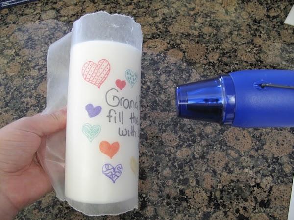 con un trozo de papel de hornear ms grande que la vela envolvemos la vela y el dibujo y tenemos presionado mientras con el secador de pelo vamos - Velas Decoradas